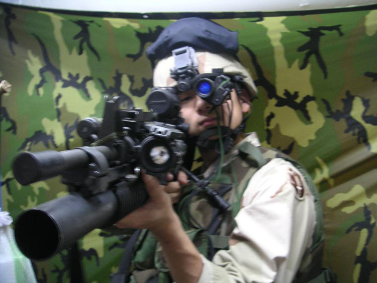 Iraq War Photo. Two things are wrong with this picture here. The red dot sight still has the cap on, and the muzzle's got a safety cap on it as well.
