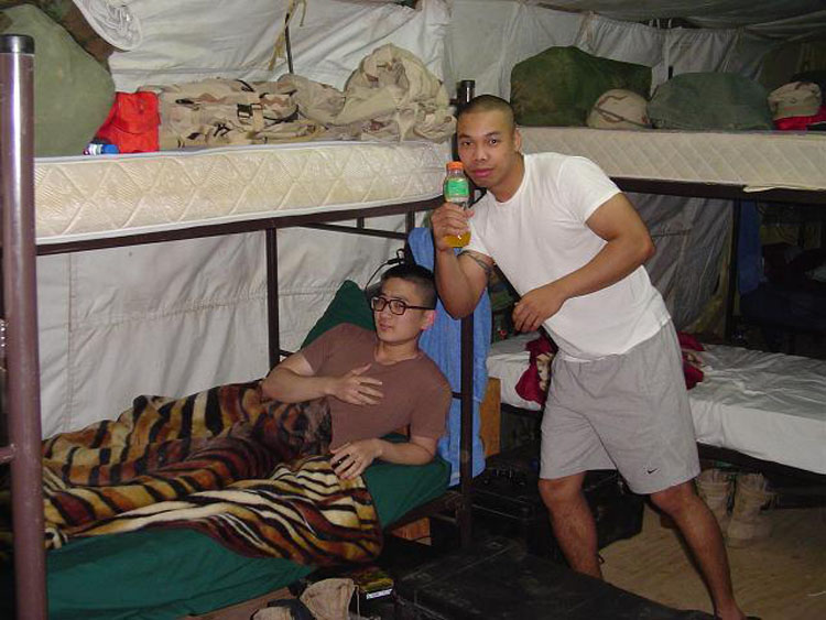 Iraq War Photo. This is when I started to get settled in some more. I bought a blanket, and had most of my stuff organized in a fairly neat matter, along with my sheet covers and pillow covers. I turned the bed sideways to give myself some more room. (Roberson on right)