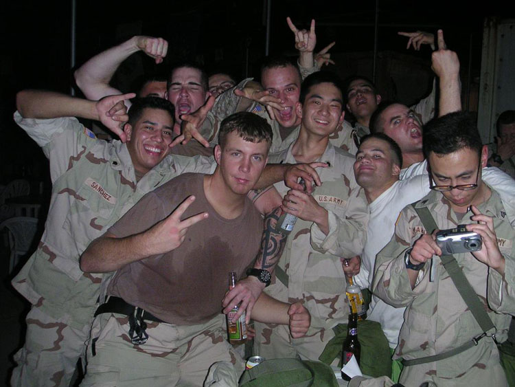 Iraq War Photo. At one point in the cantina, we were playing with the arm wrestling tables that the KBR guys had set up for us. There, the Honor Guard, Marines, us postal, and everyone in between got together to challenge everyone for a match of manhood. The highlight of my night then was my match with SGT Watson. A sniper with the Honor Guard, EIB, Airborne, Air Assault, I pointed him out. We went at it for the longest time, must have been at least 2, maybe 3 minutes and Foster started pouring beer on our hands.. But in the end, I came out victorious. A huge uproar in the postal and infantry communities ensued.