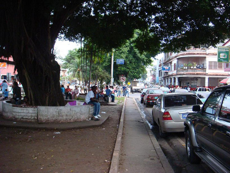 Drive to Panama Photo. This is Avenida Central, the Central Avenue of Colon.  I don't know what people do here.  They're always here, just chilling in the little 'park' running down the street.  Cars are parked on either side of the street, with no signal lights whatsoever in any part of Colon.  Just a horrible place to drive or live or visit .