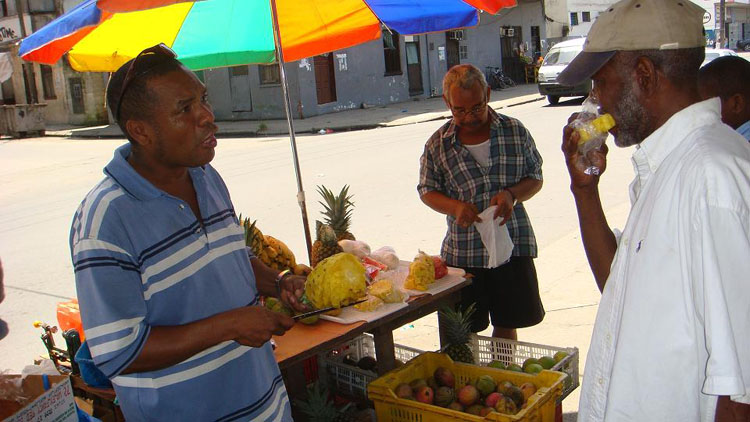 "Drive to Panama Photo. The guy on the left is a former cop.  After Van (right, eating pineapple), explains to him about what happened to me the day before, he says, ""See, now he will never come back to Colon or Panama!""  And he's right.  Unless I really want to see the third set of locks to be completed by 2014 or sit at a particular Atlantic beach resort, I will never go back to Panama.  The cop had gotten into an accident, so with his one good leg ended up selling fresh fruits and vegetables on the street."