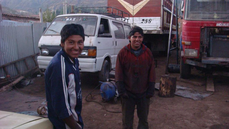 "Drive to Peru Photo. ""...I talk with Luchin (boy on the left) for a bit and realize, to my amazement, that he sleeps in the bus that I thought the mechanics were working on. It's sitting on the corner of the garage, and I ask him if I can look inside but he kindly refuses. I'm sick and tired of waiting for this guy. Luchin says [the mechanic's] not back, but that he can put it back together. The boy is 16 years old, and I don't really know what to make of it. But I don't really have much of a choice. I reluctantly tell him to put it together. I thought the man he was learning from would do most of the work and Luchin would just watch. But it was exactly the opposite. Luchin started telling the 'maestro' where all the pieces went and what not."" The car works. A 16 year old and his team of 2 other teenagers and one older mechanic who had never seen an old Mercedes Turbo Diesel sedan before put the car back together. It was a harrowing experience, having to witness many mishaps through the process and wondering, once I started to warm up the glow plugs, whether the car will start at all or not."