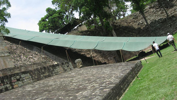 Drive to Honduras Photo. This is the second to the last picture that my Canon SD700 took before it broke. You can barely make out the steel wire that runs along the bottom on the left hand side. It's just as hard to see in real life. This is in stark contrast to thick dark ropes from all the other ruins. The green tarp running down the ruin is protecting some sort of a stairway. It is very crowded in there. The end of the tarp runs short, and there's a stone bench you can sit on, but you'd have to crouch to get there. There's also a few monuments in front of the stairs that the tarp is protecting. That monument is surrounded by invisible metal wires. The distance between the invisible metal wires surrounding the monument and the stone chair is no more than 5 feet. A man crouched down to take a picture of his girl, standing next to the stone chair, with the girl on the left side, in front of the monument. I was crossing just as he crouched to take the picture. As I ran forward to get away from the picture, my leg catches the invisible metal wire. I break the fall with my Digital camera, its lens extracted. It shuts itself down due to lens failure, and the lens never retracts. Obviously, I am not a big fan of Copan. I do not understand why the 1) tarp is so shallow, 2) there's so little distance between the monument and the stone seats when the vast openness of Copan itself can be seen clearly in the preceding picture and 3), why the monuments are surrounded by invisible metal wires hanging a foot above the ground instead of a clearly visible rope.